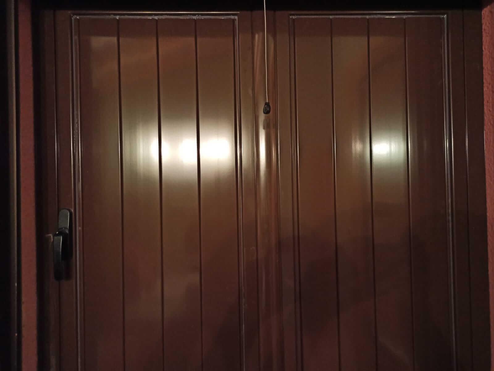 Contraventana de madera marrón, de dos hojas, totalmente cerrada. Vista desde el interior de la vivienda.