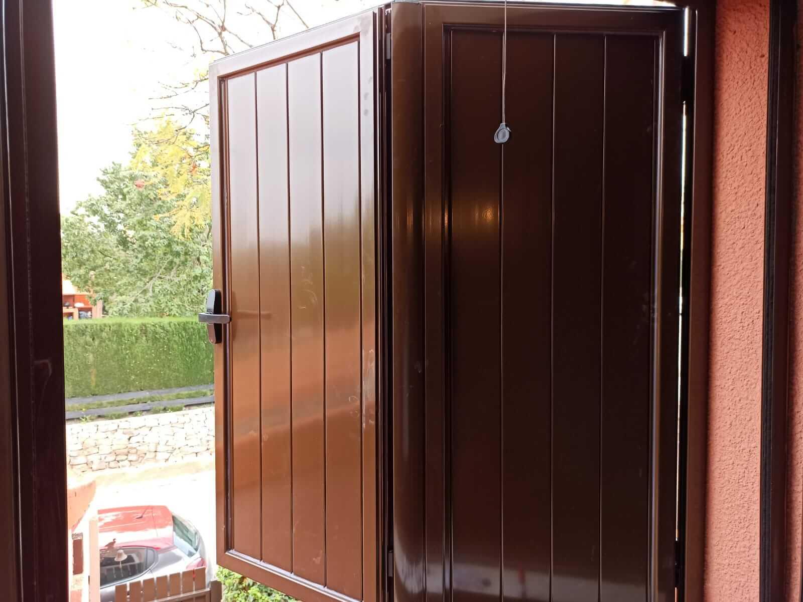 Contraventana de madera marrón de dos hojas, vista desde el interior de la vivienda plegada.
