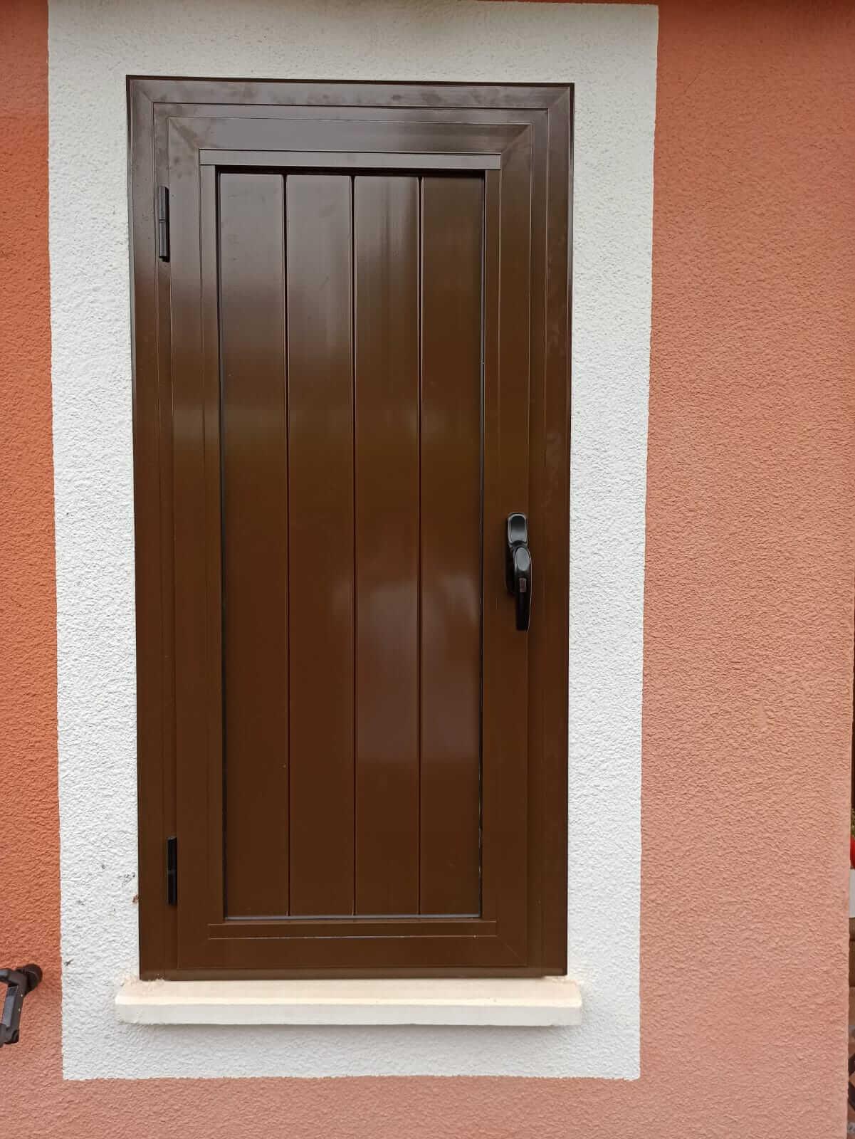 Contraventana de madera marrón de una hoja, cerrada, vista desde el exterior de la vivienda.