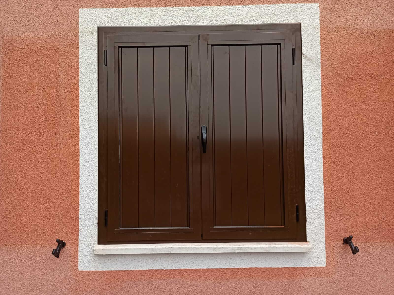 Contraventana de madera marrón de dos hojas, cerrada, vista desde el exterior de la vivienda.
