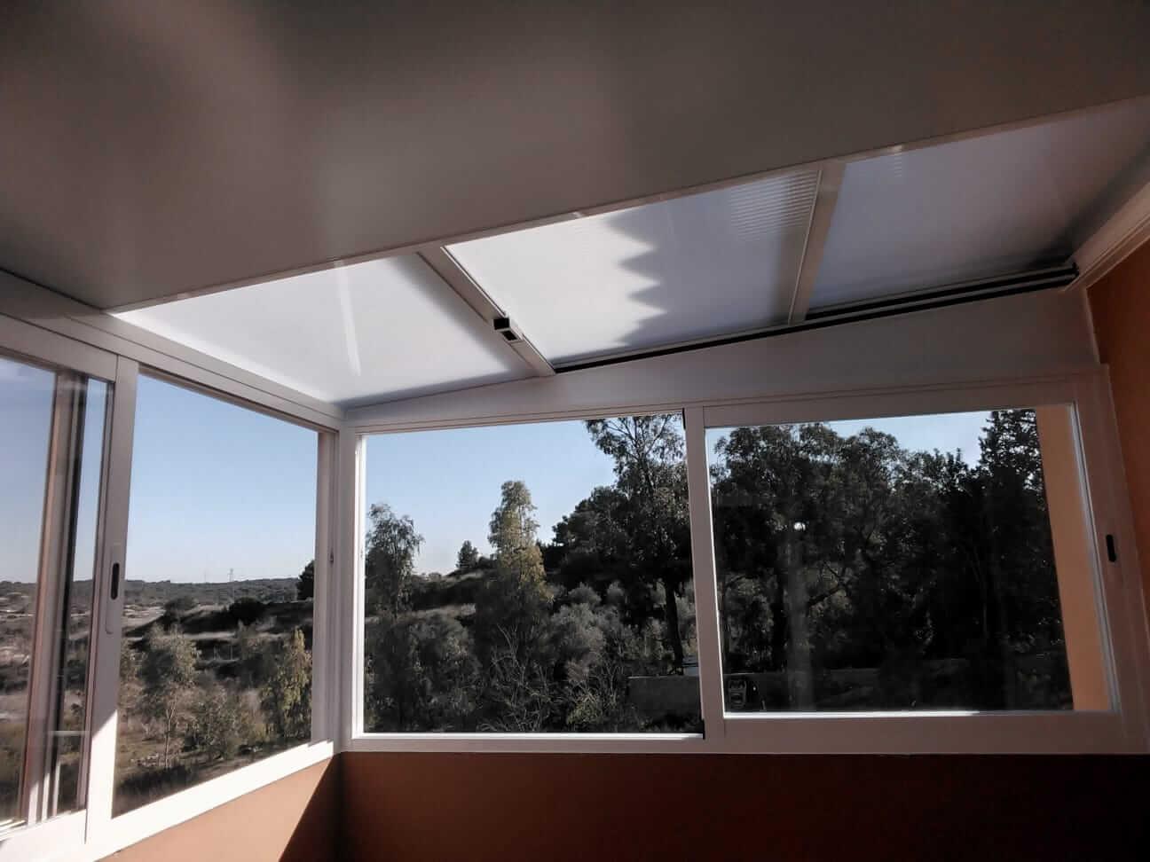Cerramiento acristalado en balcón exterior, con techo de cristal traslucido y abatible.