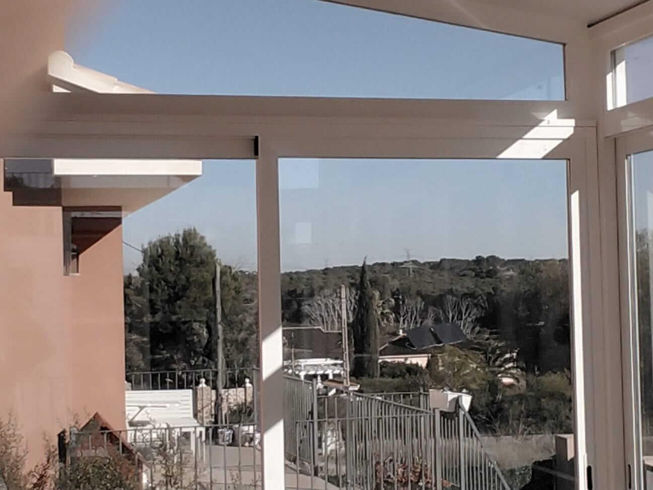 Cerramiento de cristal en balcón exterior de casa unifamiliar. Vista desde el interior de la vivienda
