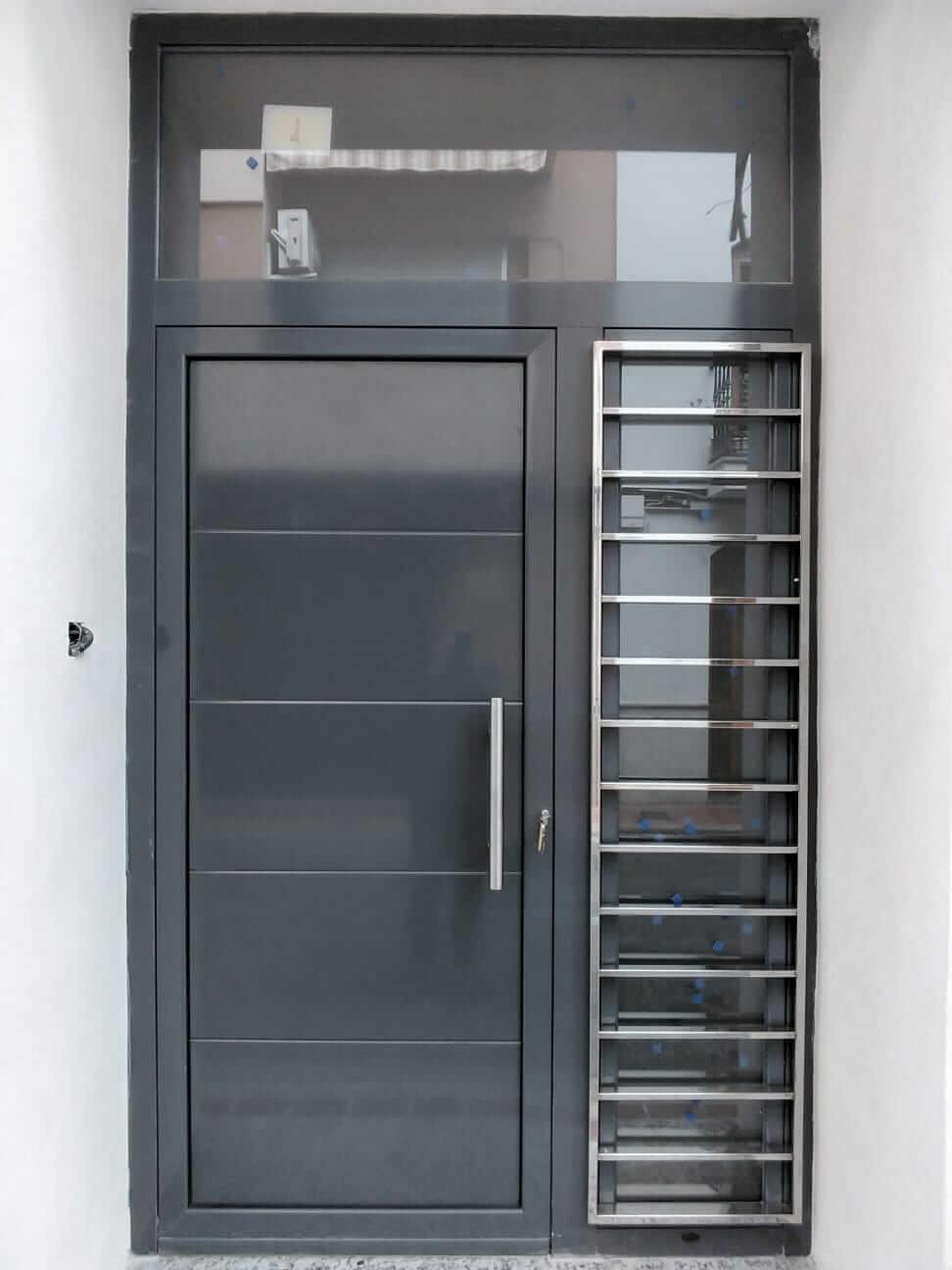 Puerta de entrada a casa unifamiliar de color gris, acristalada en un lateral y detalles en acero