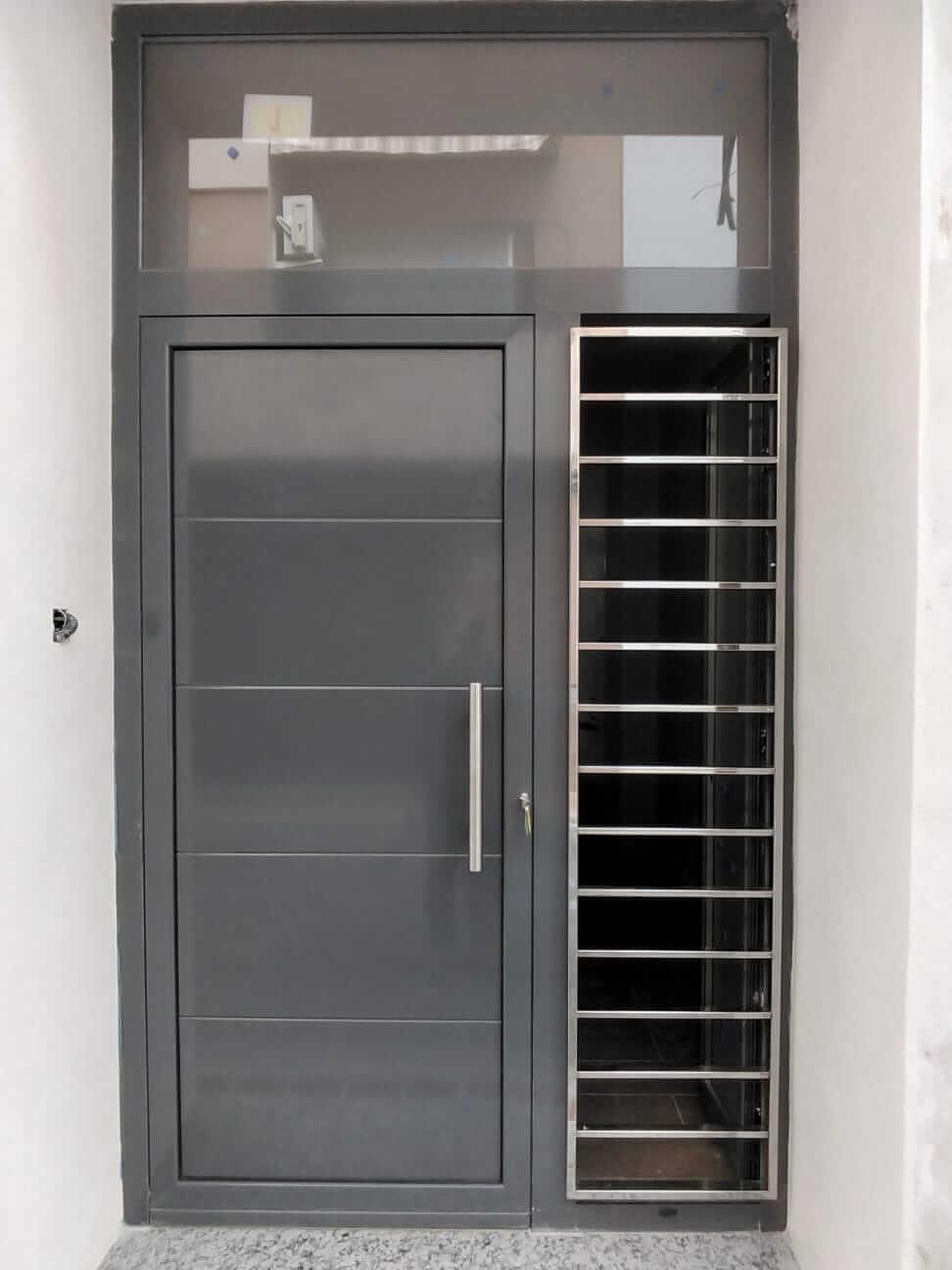 Puerta de entrada a casa unifamiliar de color gris y detalles en acero