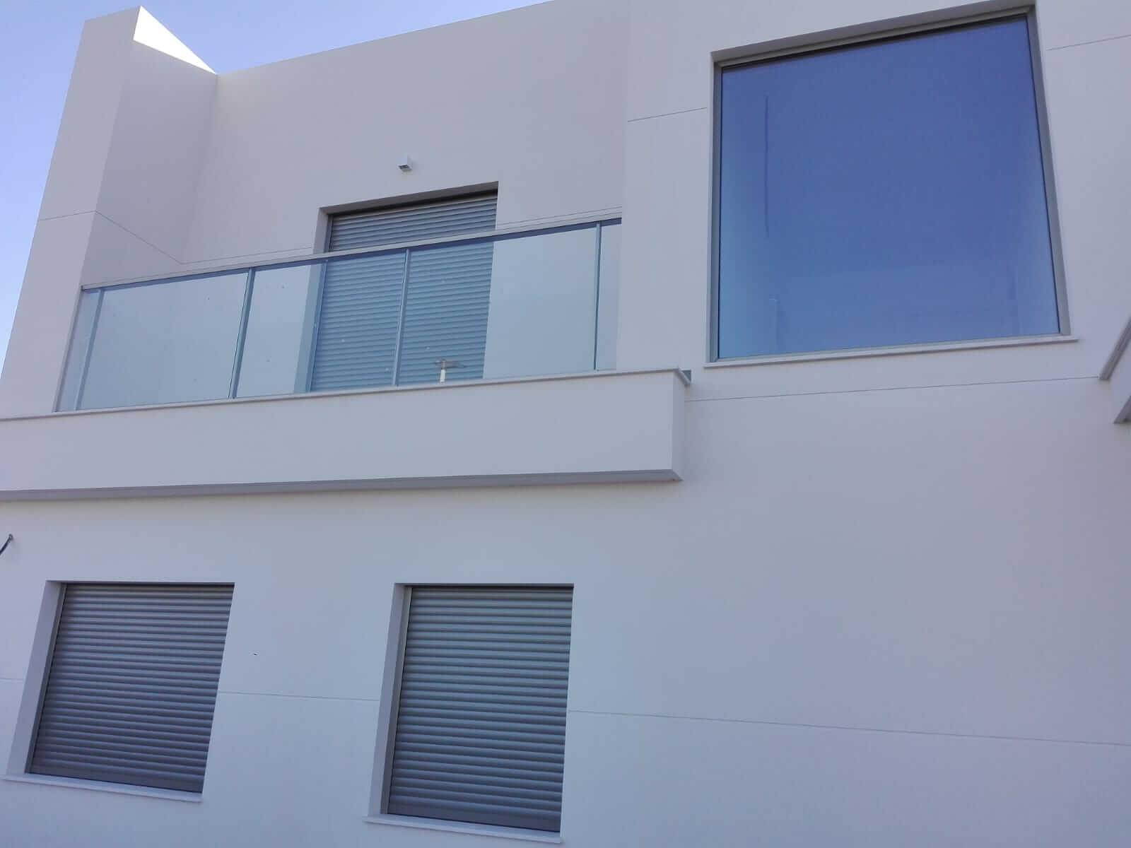 Fachada casa unifamiliar blanca, con cuatro ventanas y barandilla de balcón acristalada realizada por Finestral.