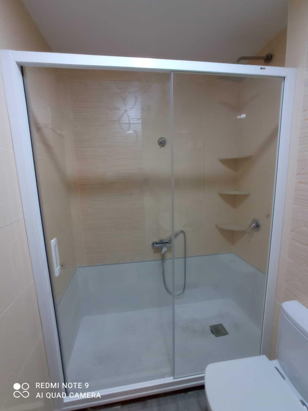 Mampara de baño de cristal transparente y marco en color blanco, colocada sobre azulejos amarillos.