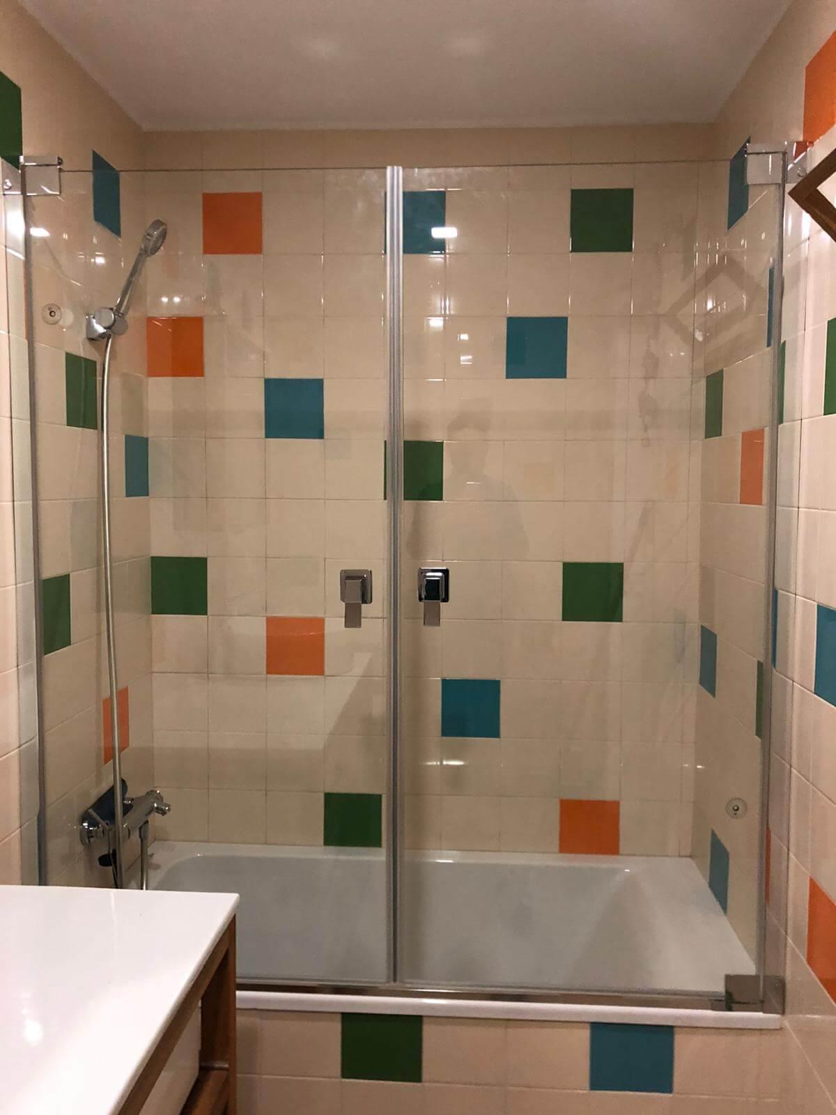 Mampara de baño de cristal transparente y marco en color acero, colocada sobre azulejos blancos, verdes y naranjas.