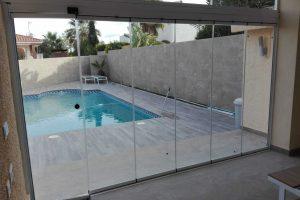 Puerta de balconera de seis hojas de cristal transparente deslizante. Vista desde interior vivienda
